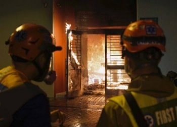 First aid volunteers try to extinguish a fire set by local residents at a building of the Fai Ming Estate, in Fanling district of Hong Kong, Sunday, Jan. 26, 2020, after the Hong Kong government announced it would requisition the unoccupied housing project to house quarantined patients of the new viral coronavirus illness.  Residents took the streets on Sunday night to oppose the plan to house quarantined patients or medical workers in their neighbourhood, that is far from Hong Kong's busy business centres. (AP Photo/Vincent Yu)