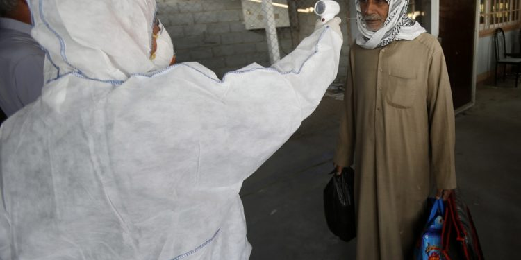 epa08231818 A member of the medical team checks the body temperature of an Iraqi man upon arrival at Shalamcheh border crossing with Iran, east of Basra city, 500 km southern Iraq on 20 February 2020. Iraqi authorites have taken action to screen those arriving at the airports and border crossings with Iran, while the Iraqi airlines canceled all flights to Iran, following the cases of the deadly Covid-19 Coronavirus diagnosed in iran. EPA/HAIDER AL-ASSADEE