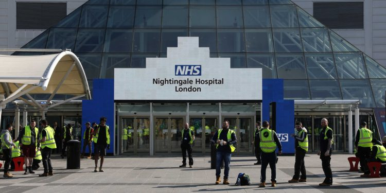 Workers are pictured outside the Excel Centre, London while it is being prepared to become the NHS Nightingale Hospital as the spread of the coronavirus disease (COVID-19) continues, in East London, Britain, March 27, 2020. REUTERS/Simon Dawson