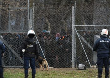 Migrants who want to cross into Greece from Turkey are gathered at the borderline as Greek riot police stand guard, at the closed Kastanies border crossing with Turkey's Pazarkule, in the region of Evros, Greece, February 28, 2020. REUTERS/Alexandros Avramidis