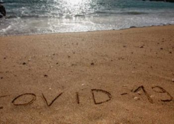 Travel and tourism concept for pandemic alert, flights and trips cancellation. Text written on the sandy beach in Algarve.