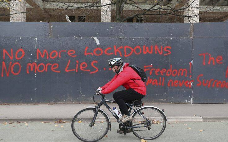 A man cycles past anti-lockdown graffiti in Manchester, England, Monday, Oct. 19, 2020 as the row over Greater Manchester region's coronavirus status continues. Britain's government says discussions about implementing stricter restrictions in Greater Manchester must be completed Monday because the public health threat caused by rising COVID-19 infections is serious and getting worse. (Peter Byrne/PA via AP)
