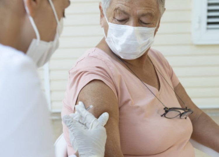 Senior woman wearing a protective face mask is getting vaccination from a female doctor with white surgical gloves and protective face mask.