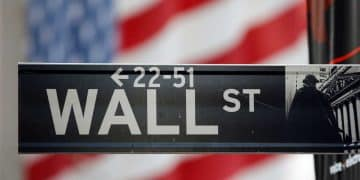 FILE PHOTO: A sign for Wall Street is seen with a giant American flag in the background across from the New York Stock Exchange November 5, 2012.   REUTERS/Chip East (UNITED STATES - Tags: BUSINESS)/File Photo