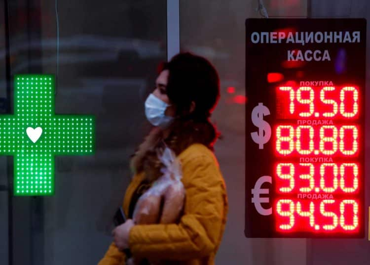 FILE PHOTO: Woman walks past a board showing currency exchange rates of the euro and U.S. dollar against the Russian rouble in Moscow, Russia November 2, 2020. REUTERS/Maxim Shemetov/File Photo