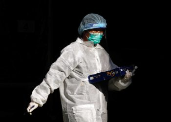 A medical worker in a protective suit walks at a makeshift community testing centre for the coronavirus disease (COVID-19), in Hong Kong, China November 30, 2020. REUTERS/Tyrone Siu