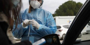 Medical personnel prepares to conduct a COVID-19 rapid test at a drive-through testing site in Athens, Friday, Dec. 11, 2020. Despite five weeks of lockdown measures, coronavirus infections remain high, putting pressure on the country's health system. (AP Photo/Thanassis Stavrakis)