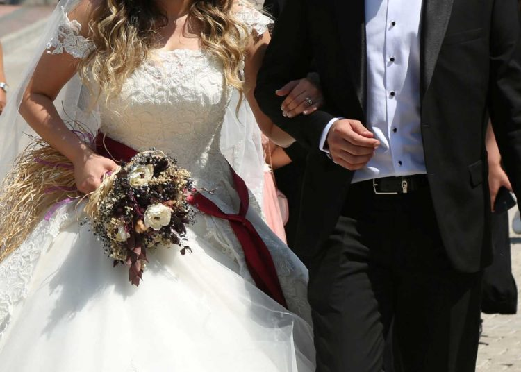 Bride Pelsin Akkoyun and groom Nizamettin Bingol, wearing protective face masks, walk following their civil wedding ceremony, amid the spread of the coronavirus disease (COVID-19), in Diyarbakir, Turkey, July 2, 2020. Turkey reopened its wedding halls in one of the final steps of reopening from the shutdown due to the coronavirus disease (COVID-19). REUTERS/Sertac Kayar