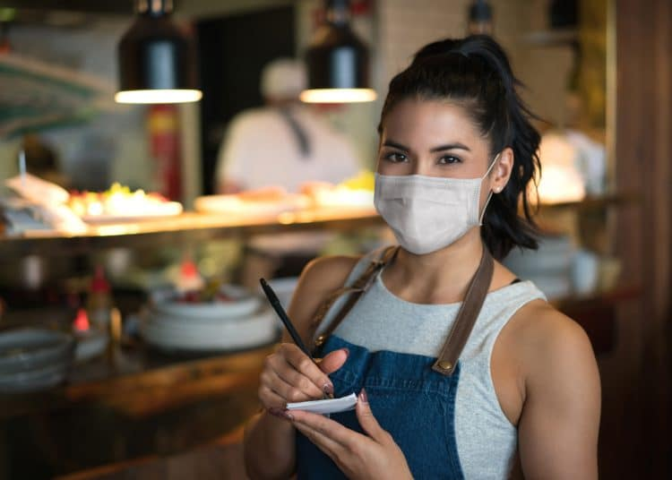 Portrait of a beautiful waitress working at a restaurant wearing a facemask while holding a notepad and looking at the camera – pandemic lifestyle concepts