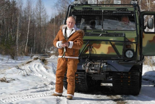 Russian President Vladimir Putin stands in front of a vehicle with Defence Minister Sergei Shoigu inside during a holiday in the Siberian taiga, Russia March 21, 2021.  Sputnik/Alexei Druzhinin/Kremlin via REUTERS ATTENTION EDITORS - THIS IMAGE WAS PROVIDED BY A THIRD PARTY.