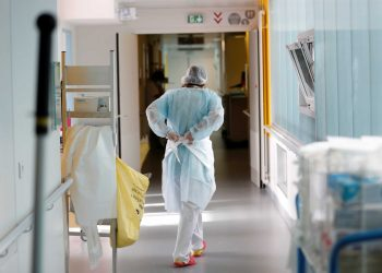 A doctor, wearing a protective mask and a protective suit, works in a pulmonology unit at the hospital in Vannes where patients suffering from the coronavirus disease (COVID-19) are treated, France, October 12, 2020. REUTERS/Stephane Mahe