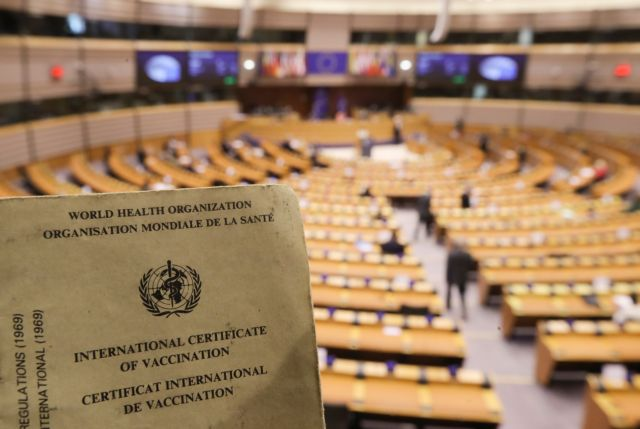 epa09164738 An international certificate of Vaccination of the World Health Organization (WHO) for Yellow fever with European Parliament hemicycle in background as members of the Parliament debate of legality of the Digital green certificate, an international certificate of vaccination for Covid-19 during plenary session of the European Parliament in Brussels, Belgium, 28 April 2021.  EPA/OLIVIER HOSLET