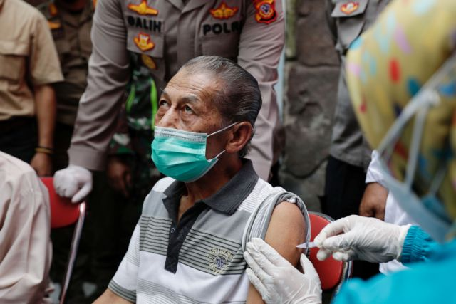 Inan Rustandi, 72-year-old local of Sindanglaya village, reacts as he receives his first dose of China's Sinovac Biotech vaccine for the coronavirus disease (COVID-19) outside his house, during a door-to-door vaccination in Cianjur regency, West Java province, Indonesia, June 15, 2021. REUTERS/Willy Kurniawan