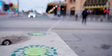 Coronavirus graffiti is seen in front of a mostly-empty city centre street during morning commute hours on the first day of a seven-day lockdown as the state of Victoria looks to curb the spread of a coronavirus disease (COVID-19) outbreak in Melbourne, Australia, May 28, 2021.  REUTERS/Sandra Sanders