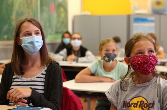 Schoolgirls of the fifth year voluntarily wear protective face masks inside their classroom as schools re-open after summer holidays and the lockdown due to the outbreak of the coronavirus disease (COVID-19) at the Karl-Rehbein high school in Hanau, Germany, August 17, 2020.   REUTERS/Kai Pfaffenbach