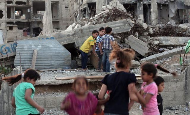 epa04778048 Palestinian children play between their destroyed homes, damaged during the Israeli-Hamas conflict of 2014, in Al Shejaeiya neighbourhood, eastern Gaza City, 31 May 2015. Israel will do whatever is needed to ensure that its southern border area with the Gaza Strip remains quiet, Israeli Prime Minister Benjamin Netanyahu warned last week, after a Gaza armed group launched a Grad missile at the southern Israeli town of Gan Yavneh. It was the first Grad missile launched since the July-August 2014 war.  EPA/MOHAMMED SABER